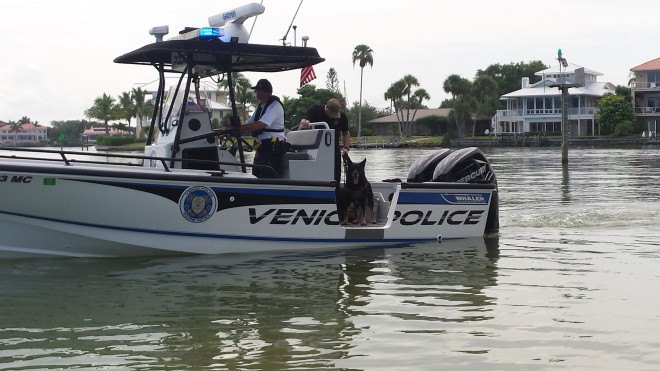 A Venice Police boat on the water with houses in the background.